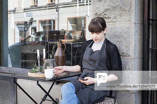 Junge Besitzerin mit Smartphone beim Sitzen mit Kaffeetasse am Tisch gegen den Laden