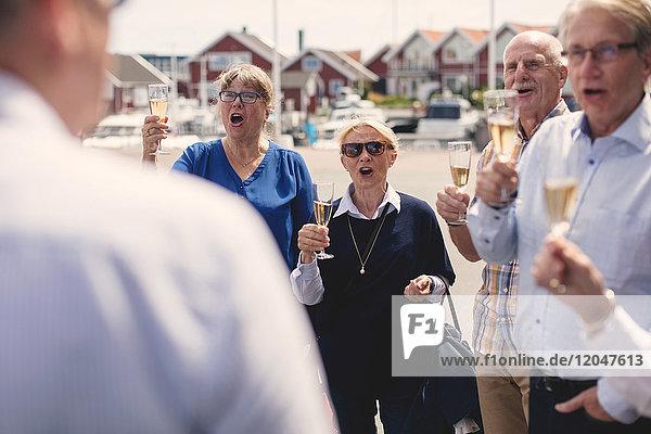 Männliche und weibliche Freunde jubeln beim Rösten von Champagnerflöten im Freien.