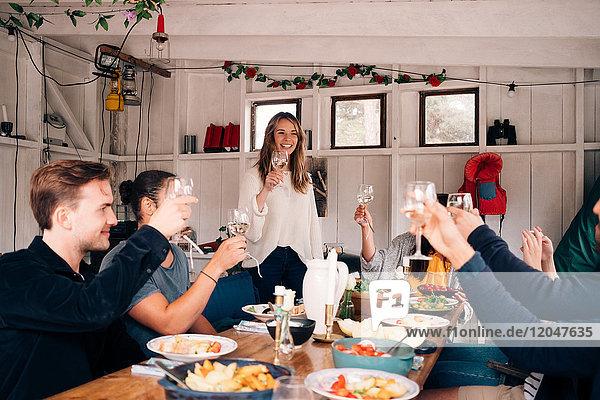 Glückliche männliche und weibliche Freunde  die in der Hütte Weingläser züchten.