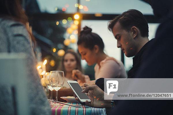 Beschnittenes Bild eines Mannes  der ein Smartphone benutzt  während er unter Freunden am Esstisch sitzt.