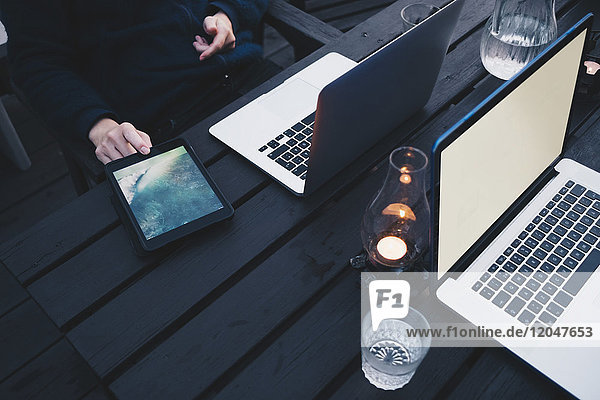 Frau mit digitalem Tablett per Laptop auf Holztisch in der Ferienvilla
