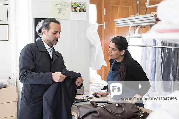 Reife männliche Besitzerin mit Anzug für Unternehmerin bei Laundromat