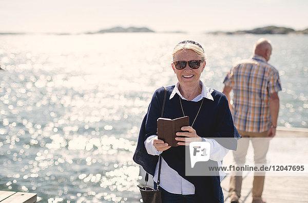 Porträt einer lächelnden Seniorin mit Sonnenbrille  die ihr Handy gegen den See hält.