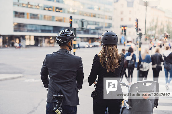 Rear view of business colleagues with bicycles on street in city