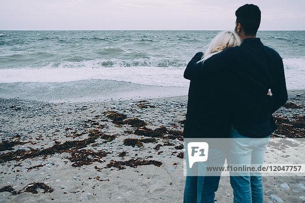 Rückansicht eines jungen Paares  das am Strand steht.