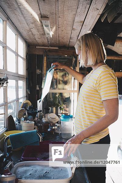 Seitenansicht der Frau beim Geschirrspülen in der Küche der Ferienvilla