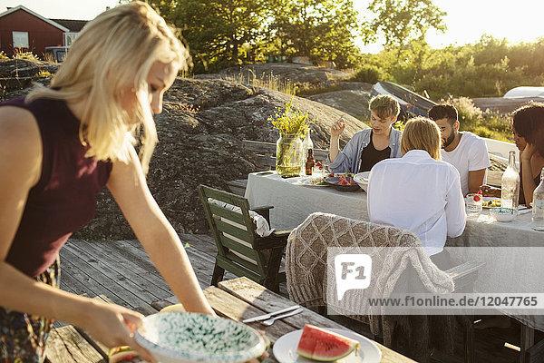 Frau pflückt Wassermelonenscheibe,  während Freunde am Picknicktisch im Hafen essen.