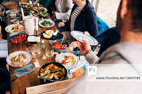 Abgeschnittenes Bild des Mannes  der während der Mittagsparty den Teller an einen Freund weitergibt.