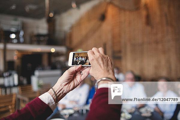 Abgeschnittenes Bild einer älteren Frau  die Freunde mit dem Smartphone im Restaurant fotografiert.