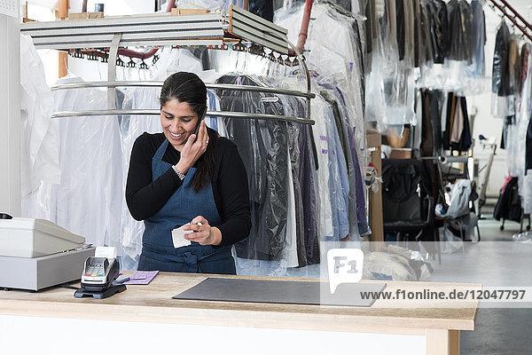 Lächelnde  reife Putzfrau  die im Waschsalon auf dem Smartphone spricht.