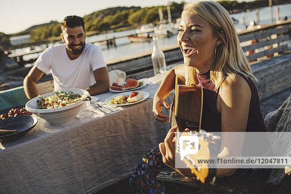 Fröhliche Frau spielt Gitarre  während ein Freund an einem sonnigen Tag am Picknicktisch sitzt.