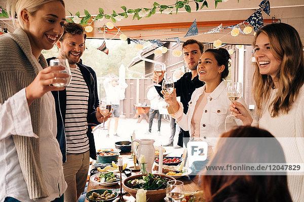 Junge männliche und weibliche Freunde  die lächeln  während sie Trinkgläser in der Hütte halten.