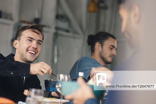 Happy young male friends sitting at dining table