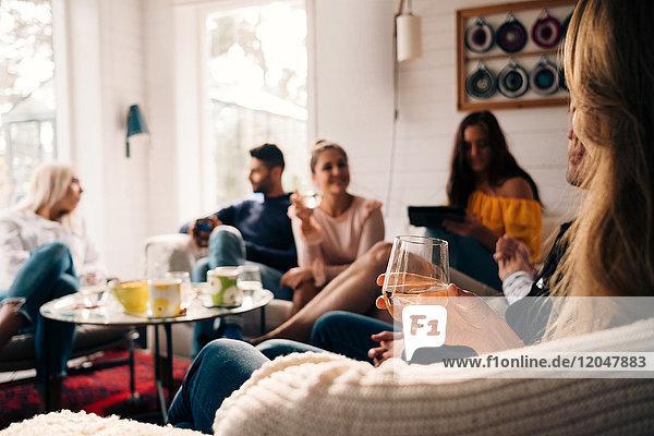 Frau hält Glas  während sie mit Freunden in der Hütte sitzt.