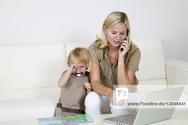 Mother Using Laptop and Cell Phone  Toddler Standing Beside Her Crying