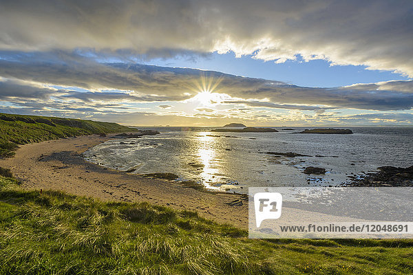 Sun shining over bay with sandy beach at sunset in North Berwick at Firth of Forth in Scotland  United Kingdom