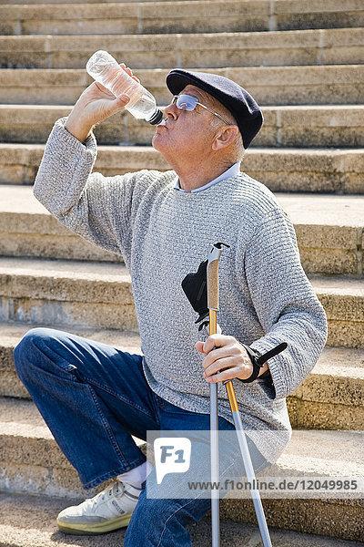 Nordic Walker Taking a Break and Drinking Bottled Water