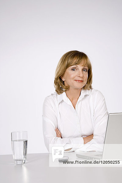 Woman with Glass of Water  Laptop Computer and Cellular Phone