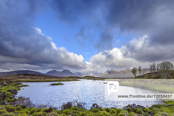 Moor landscape with lake and cloudy sky with mountains in the background at Rannoch Moor in Scotland  United Kingdom