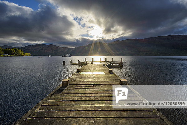 Wooden jetty on lake with dramatic clouds at sunrise at Loch Lomond in Scotland  United Kingdom