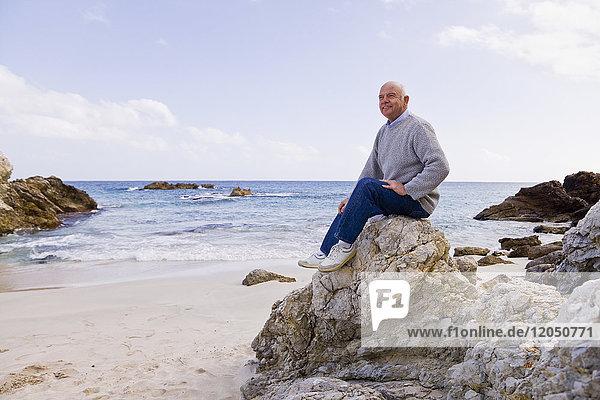Man Sitting on Rocks on the Beach