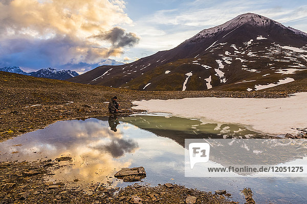 A backpacker pauses for rest beside a puddle while crossing over an unnamed pass in the Brooks Range under the midnight sun at 12:14 a.m.; Alaska  United States of America