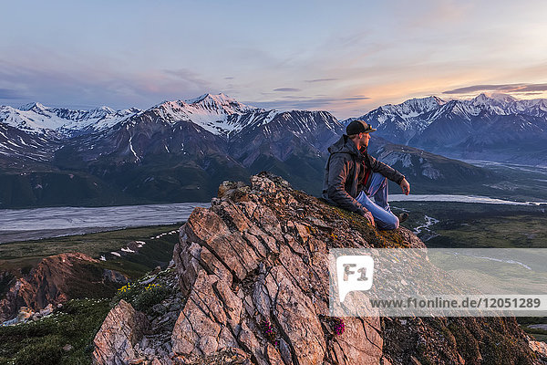 A man observes a tranquil sunset from an alpine perch in the Alaska Range high above the Delta River; Alaska  United States of America