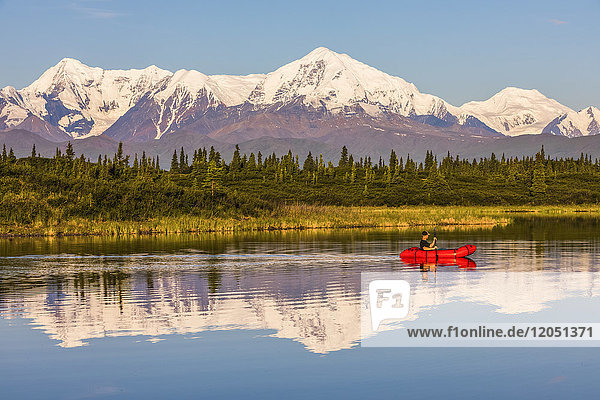 A man paddles across Donnelly Lake in a pack raft with Mt. Moffit and the Alaska Range reflecting on the water; Alaska  United States of America