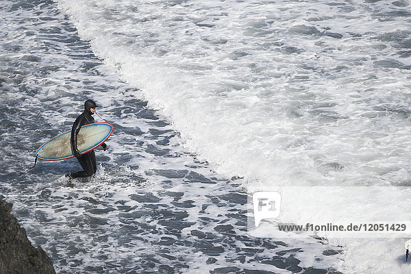 Surfer With Surfboard Enters Waters Of The Kenai Peninsula Outer Coast  Southcentral Alaska  USA