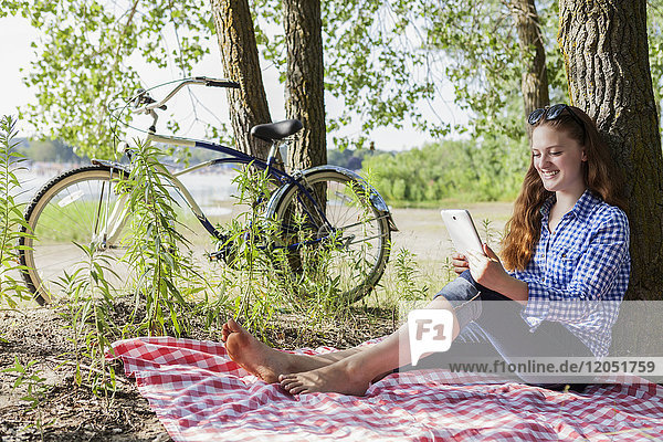 Teenage girl sitting on picnic blanket using a tablet at Woodbine beach in summer; Toronto  Ontario  Canada