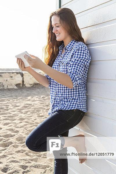Girl using tablet at Woodbine beach in summer; Toronto  Ontario  Canada