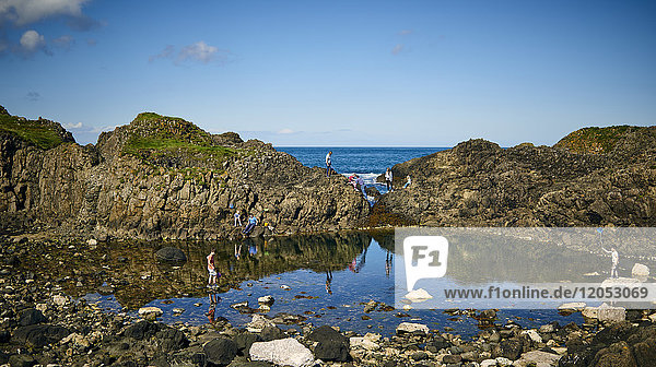 Children Playing In The Tide Pools Along The Coast Of Northern Ireland; Ireland