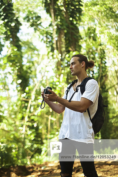 A young man stands on a trail wearing a backpack and taking a picture with a camera while on a hike; Hawaii  United States of America