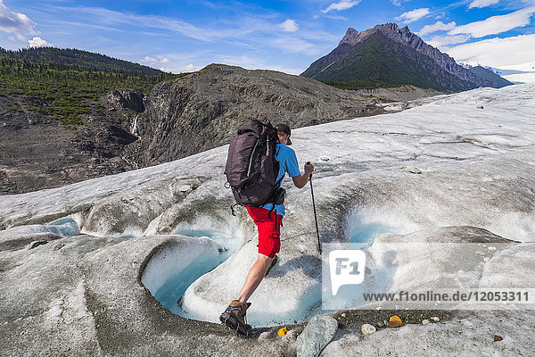 A backpacker crosses a stream on the surface of Root Glacier in Wrangell-St. Elias National Park. Donoho Peak is in the background; Alaska  United States of America