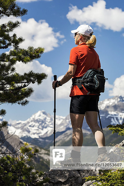 Female Hiker Standing On Top Of Mountain Ridge Overlooking Mountain Range With Clouds And Blue Sky; Banff  Alberta  Canada