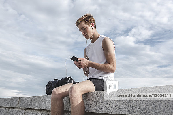 Junger Sportler auf einer Wand sitzend mit Handy und Kopfhörer