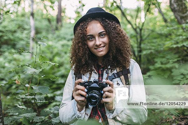 Porträt eines lächelnden Teenagermädchens beim Fotografieren in der Natur