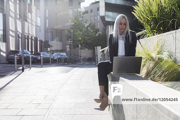 Young businesswoman sitting on a wall in the city using laptop