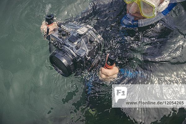Mann mit Unterwasser-DSLR-Kameragehäuse im See