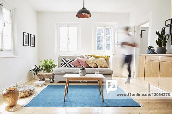Mann  der in einem hellen  modernen Wohnzimmer in einem alten Landhaus spazieren geht.