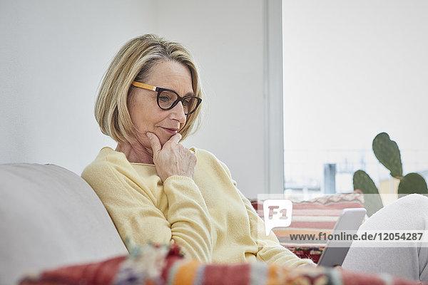 Reife Frau zu Hause auf dem Sofa mit Blick auf das Handy