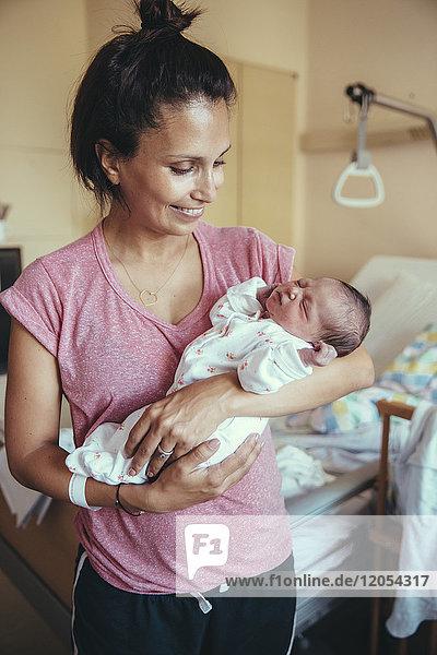 Glückliche Mutter  die ihr neugeborenes Baby im Krankenhaus hält