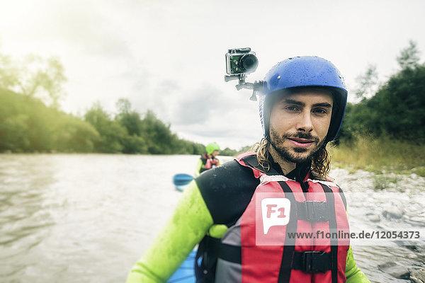 Deutschland  Bayern  Allgäu  Porträt eines selbstbewussten jungen Mannes mit Action-Cam-Kajak auf der Iller