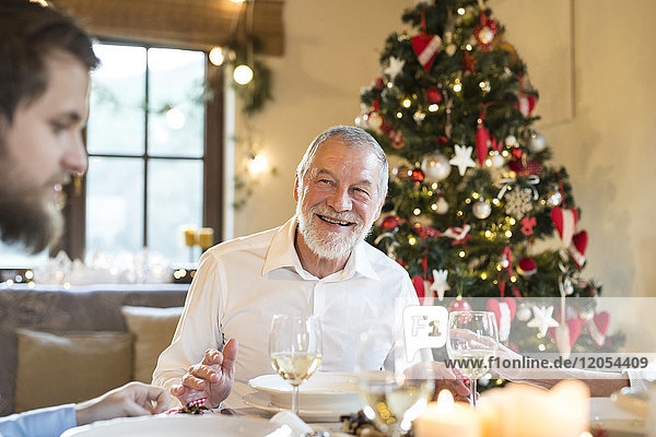 Lächelnder älterer Mann  der den erwachsenen Sohn am Weihnachtstisch ansieht.