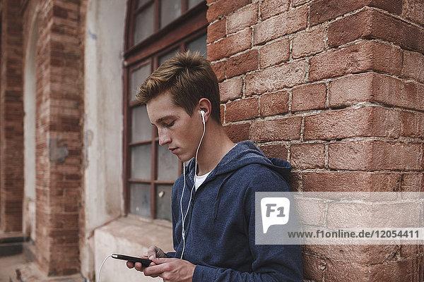 Junger Mann mit Handy und Kopfhörer im Backsteingebäude