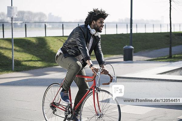 Lächelnder Mann auf dem Fahrrad am Flussufer