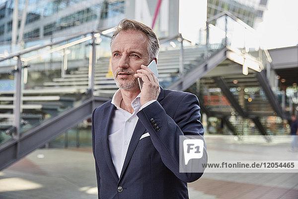 Geschäftsmann mit Smartphone am Flughafen