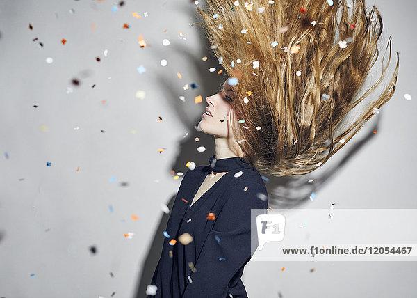 Junge Frau beim Haarewerfen unter Konfetti-Dusche