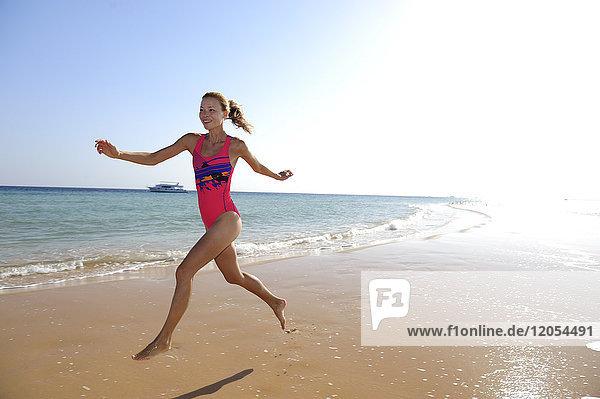 Ägypten  Soma Bay  glückliche Frau  die am Strand rennt