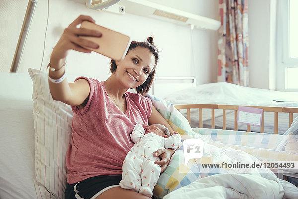 Mutter nimmt einen Selfie mit ihrem neugeborenen Baby im Krankenhausbett mit.
